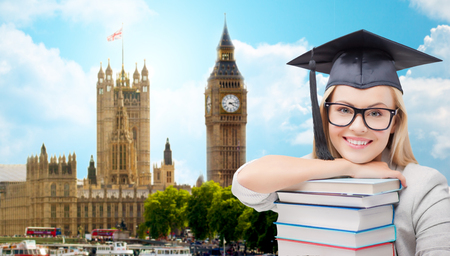 education, school, knowledge and people concept - picture of happy student girl or woman in trencher cap with stack of books over houses of parliament in london city background