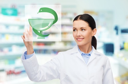 health facility: medicine, pharmacy, people, health care and pharmacology concept - happy young woman pharmacist with medical symbol of snake and cup over drugstore background Stock Photo