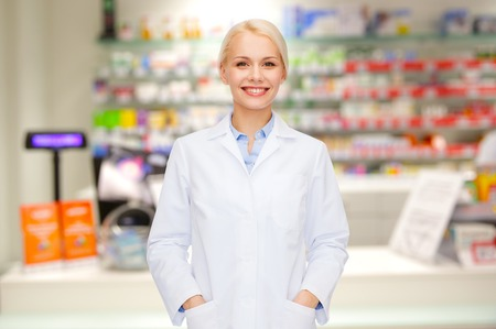 medicine, pharmacy, people, health care and pharmacology concept - happy young woman pharmacist over drugstore background Foto de archivo