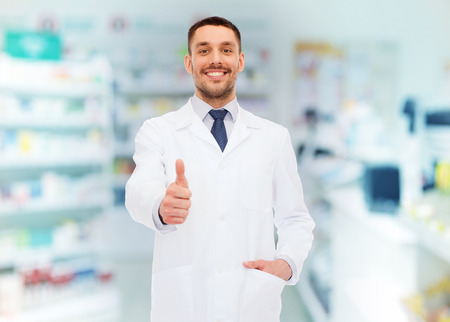 background person: medicine, pharmacy, people, health care and pharmacology concept - smiling male pharmacist in white coat showing thumbs up over drugstore background