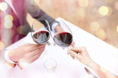 restaurant, les gens, la fête et la fête concept - gros plan d'un jeune couple avec des verres de vin rouge au restaurant pendant les vacances lumières fond