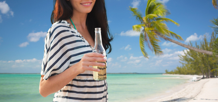 nonalcoholic beer: summer vacation, holidays, drinks and people concept - close up of smiling young woman drinking from bottle on tropical beach