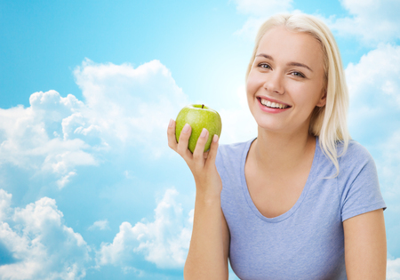 slim girl: healthy eating, organic food, fruits, diet and people concept - happy woman eating green apple over blue sky and clouds background