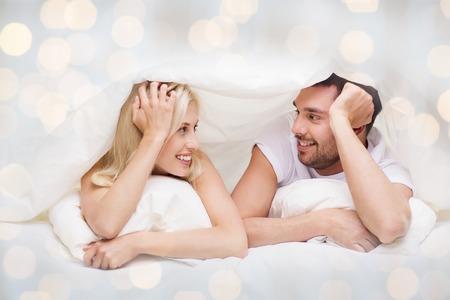 jovenes enamorados: las personas, la familia, la hora de acostarse y el concepto de la felicidad - pareja feliz acostado en la cama cubierto con una manta sobre la cabeza y hablar en casa sobre fondo de las luces Foto de archivo