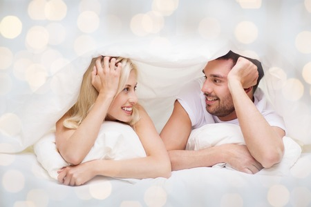 people, family, bedtime and happiness concept - happy couple lying in bed covered with blanket over head and talking at home over lights background Stock Photo