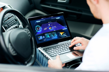 transport, modern technology and people concept - man using navigation system on laptop computer in car Reklamní fotografie