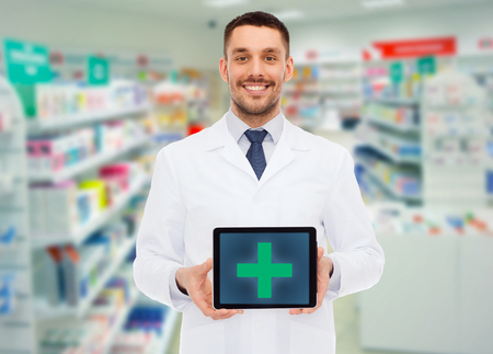 medicine, pharmacy, people, health care and pharmacology concept - smiling male doctor showing tablet pc computer with cross symbol on screen over drugstore background