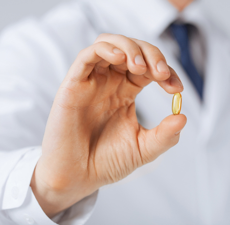 doctor fish wellness fish: picture of doctor hand showing one capsule