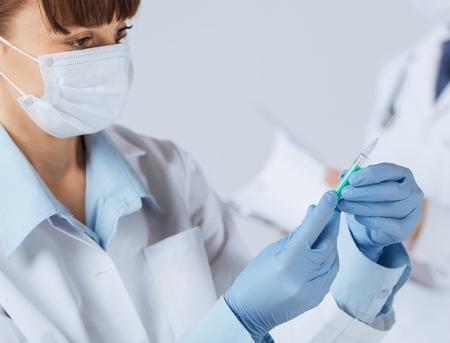 注射シリンジを保持している女性医師のクローズ アップ 写真素材
