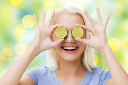 summer diet: healthy eating, organic food, fruit diet, comic and people concept - happy woman having fun and covering her eyes with lime slices over summer green holidays lights background