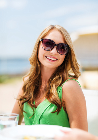 woman beach dress: summer holidays and vacation - girl in shades in cafe on the beach