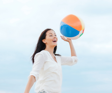 woman resting: summer holidays, vacation and beach activities concept - girl with ball on the beach Stock Photo