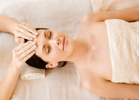 health resort treatment: close up of woman in spa salon getting face treatment