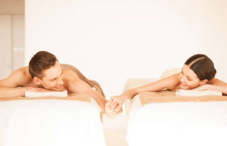 spa therapy: picture of couple in spa salon lying on the massage desks