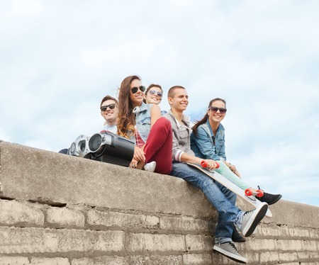 youth group: summer holidays and teenage concept - group of teenagers hanging outside Stock Photo