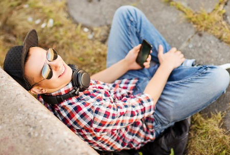 teenagers: summer holidays, teenage and technology concept - teenager with headphones and smartphone outside