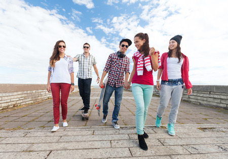 teenage: summer holidays and teenage concept - group of teenagers with skates outside Stock Photo