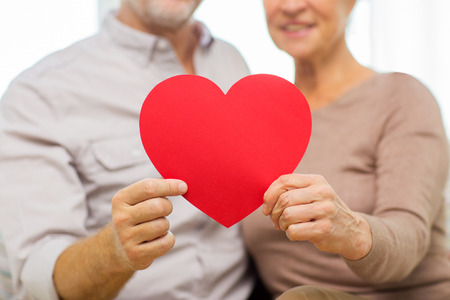 heart: family, holidays, valentines day, age and people concept - close up of happy senior couple holding big red paper heart shape cutout at home