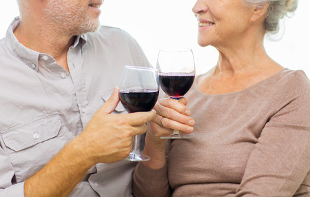 elderly people: family, holidays, drinks, age and people concept - close up of happy senior couple clinking glasses with red wine at home