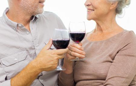 familia, días de fiesta, las bebidas, la edad y el concepto de la gente - cerca de feliz altos vasos tintinean de los pares con el vino rojo en el país