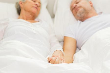 pareja durmiendo: la familia, la hora de dormir, de reposo, la edad y el concepto de la gente - Primer plano de pareja de edad tendido en el mal y durmiendo en su casa Foto de archivo