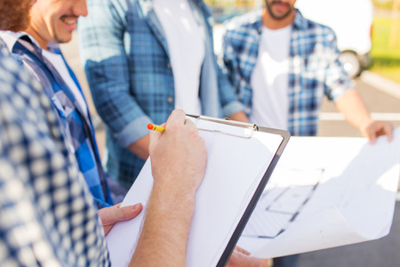 people development: building, construction, development, teamwork and people concept - close up of builders with clipboard and blueprint Stock Photo