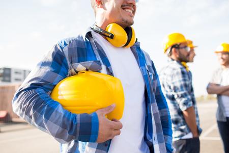 건물, 보호 장비 및 사람들이 개념 - 건설 현장에서 노란색 hardhat 또는 헬멧을 들고 작성기의 폐쇄