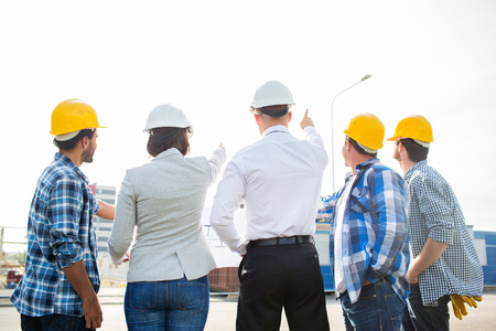 contractors: business, building, teamwork and people concept - group of builders and architects in hardhats with blueprint on construction site