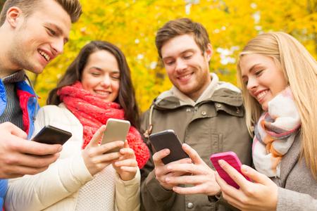 vacaciones, la gente, la tecnología y el concepto de la amistad - grupo de amigos sonriendo con los teléfonos inteligentes en el otoño de parque
