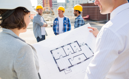 construction, architecture, business, teamwork and people concept - close up of architects with blueprint at building site