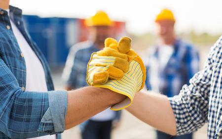 la construcción, el trabajo en equipo, la colaboración, el gesto y la gente concepto - cerca de las manos de los constructores en los guantes que se saludan con apretón de manos en la obra de construcción
