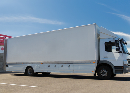 parking facilities: transportation, freight transport, advertisement and vehicle parts concept - truck on city parking