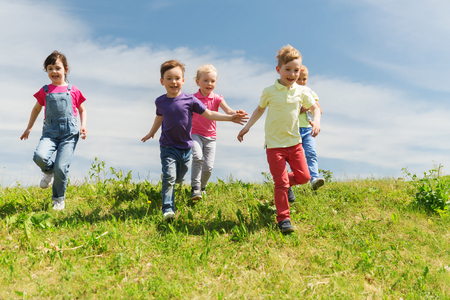 summer, childhood, leisure and people concept - group of happy kids playing tag game and running on green field outdoors Stockfoto