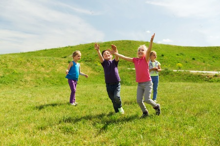 summer, childhood, leisure and people concept - group of happy kids playing tag game and running on green field outdoors Foto de archivo