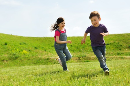 children playing outside: summer, childhood, leisure and people concept - happy little boy and girl playing tag game and running outdoors on green field