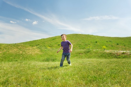 summer, childhood, leisure and people concept - happy little boy running on green field outdoors Foto de archivo