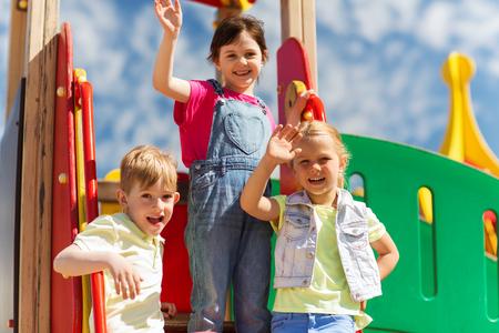 ropa de verano: verano, la infancia, el ocio, la amistad y el concepto de la gente - grupo de niños felices agitando las manos en el parque infantil