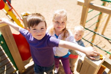 niño trepando: verano, la infancia, el ocio, la amistad y el concepto de la gente - Grupo de niños felices en el patio de los niños