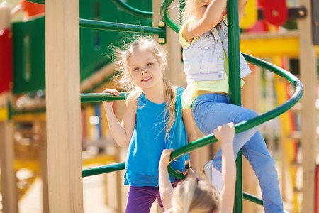 girls friends: summer, childhood, leisure, friendship and people concept - group of happy kids on children playground climbing frame
