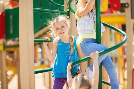 chicas sonriendo: verano, la infancia, el ocio, la amistad y el concepto de la gente - grupo de ni�os felices en el patio de los ni�os columpio