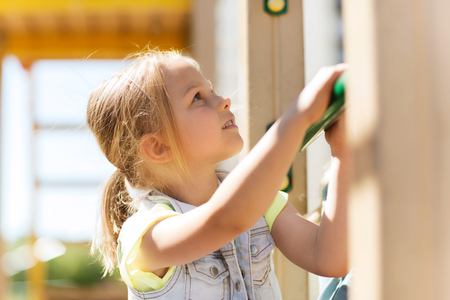 beautiful preteen girl: summer, childhood, leisure and people concept - happy little girl on children playground climbing frame