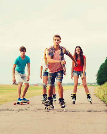 rollerblading: holidays, vacation, love and friendship concept - group of smiling teenagers with roller skates and skateboard riding outdoors