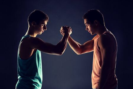 sport, competition, strength and people concept - young men wrestling Stock Photo