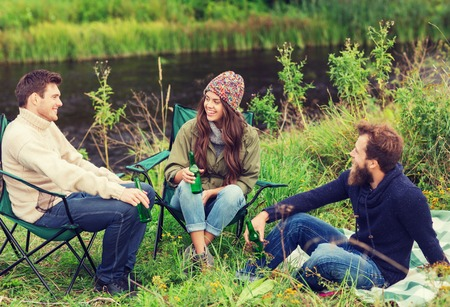 talking people: adventure, travel, tourism, friendship and people concept - group of smiling tourists drinking beer in camping