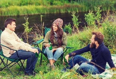 personas comunicandose: aventura, los viajes, el turismo, la amistad y el concepto de la gente - grupo de turistas sonrientes bebiendo cerveza en el camping