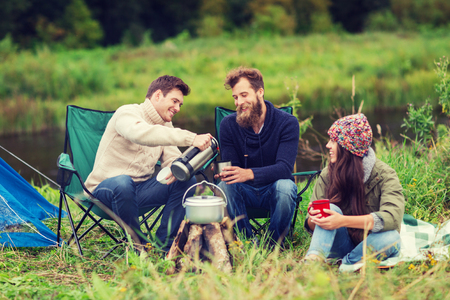 thermos: adventure, travel, tourism and people concept - group of smiling friends cooking food in dixie sitting around bonfire outdoors