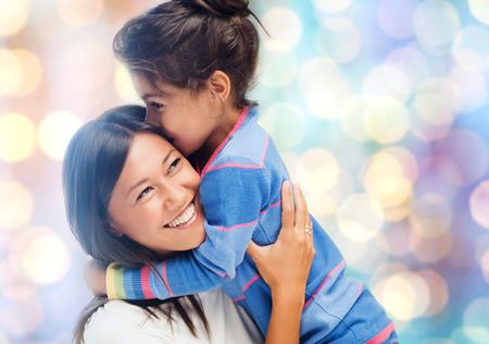 madre e hija: la gente, la maternidad, la familia y el concepto de la adopción - feliz madre e hija abrazos durante las vacaciones azules fondo de las luces
