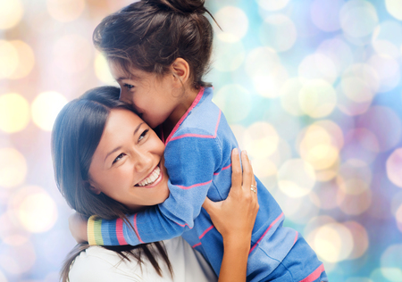 latin mother: people, motherhood, family and adoption concept - happy mother and daughter hugging over blue holidays lights background Stock Photo