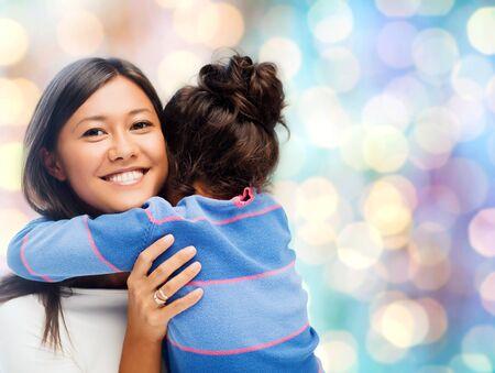 la gente, la maternidad, la familia y el concepto de la adopción - feliz madre e hija abrazos durante las vacaciones azules fondo de las luces