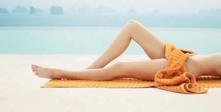 nue plage: les gens, l'été, la beauté et de vacances concept - close up de jambes de femme avec une serviette orange sur la plage ou à la piscine station